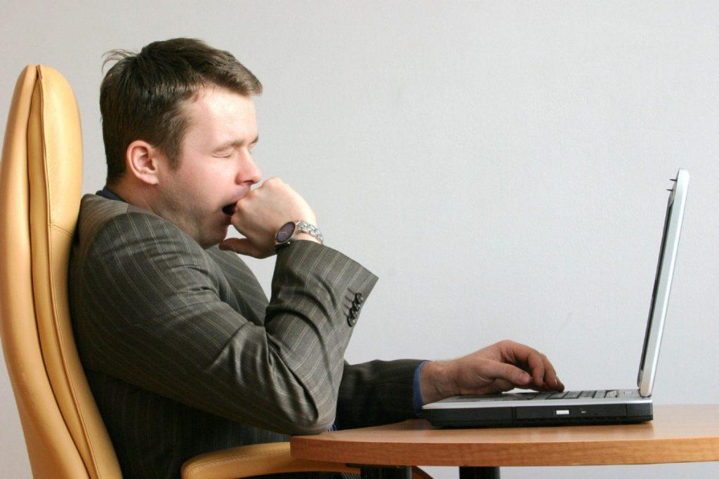 SHUTTERSTOCK IMAGE TORONTO STAR USE ONLY MAN YAWNING AT LAPTOP COMPUTER